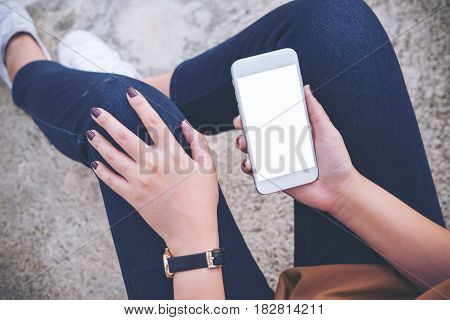 Mockup image of a woman sitting on the street and holding mobile phone with blank white screen