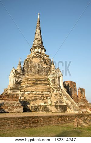 One of the three ancient stupas of the Buddhist temple Wat Phra Si Sanphet in the rays of the setting sun. Ayutthaya, Thailand