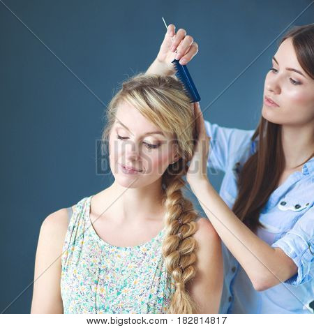 Young woman hairdresser do hairstyle girl in salon .