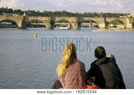 A young couple admire the view by the river