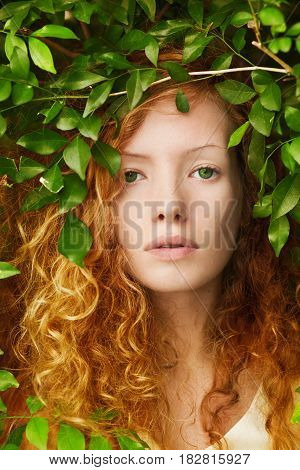 Caucasian Curly red-haired girl fairy in nature