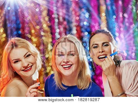 Three happy girls holding carnival whistles and celebrating party