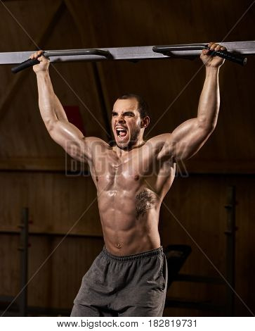 Young tired muscular man doing chin-ups and screaming