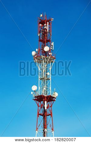 Cellular tower with antenna in red and white on a background of pure blue sky