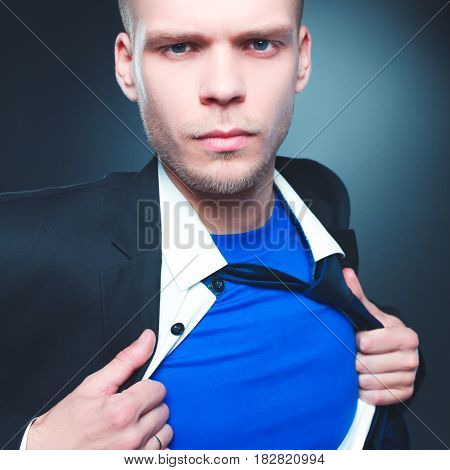 Young businessman acting like a super hero and tearing his shirt, isolated on gray background .