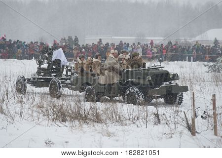 LENINGRAD REGION, RUSSIA - JANUARY 15, 2017: The female crew of an anti-aircraft gun is put forward for position. Episode of the military historical reconstruction of the battles for the breakthrough of the siege of Leningrad during the Great Patriotic Wa