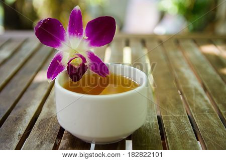 Violet dendrobium orchid flower beside a jasmine ceramic tea cup on wooden table with bright background