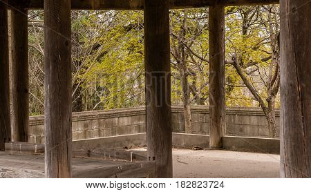 Inside view of old oriental style covered pavilion surrounded by a concrete wall in an overgrown woodland area in South Korea.