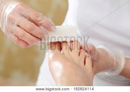 Pedicure, beautiful healthy nails. Sawing nails, woman with a beautician. Woman in a beautician at a pedicure