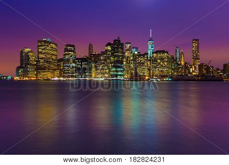 Manhattan skyline at night with colored reflections in water, New-York, USA