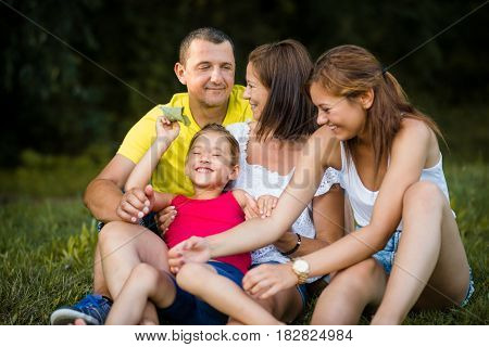 Happy family of four sitting on grass during summertime
