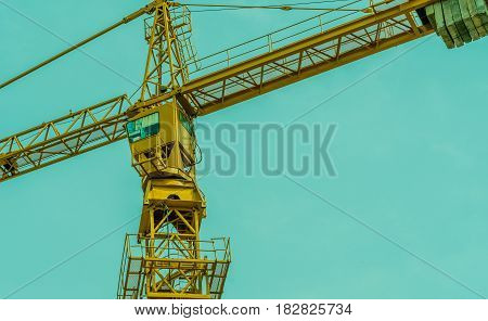 Large yellow construction crane with a background of a clear blue sky.