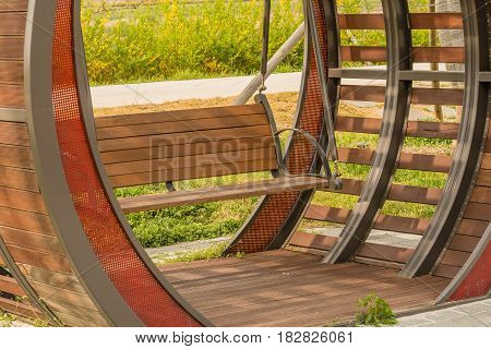 Closeup of wooden park bench swing in wooden enclosure with lush foliage in background.