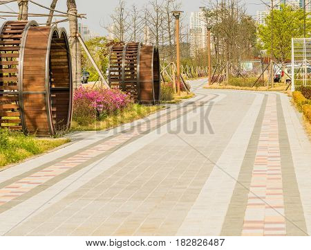 Concrete brick walkway through urban public park with highrise buildings in the background.