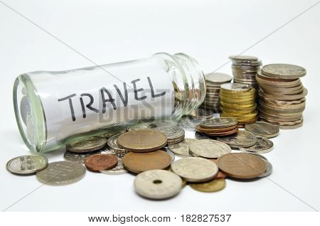 Travel Lable In A Glass Jar With Coins Spilling Out