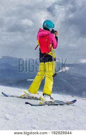 skier makes a photo of mountain scenery while standing on top of a mountain