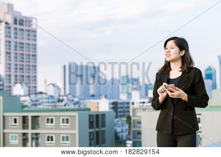 Business Asian Women Use Telephone On Top Of Building