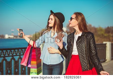 Two girls walking with shopping bags on city streets at sunny day