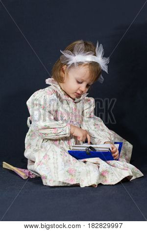 Cute little girl is reading a book