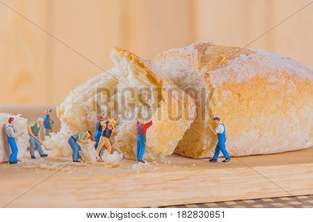 concept idea image of mini figure dolls making French Baguette bread on slice board.