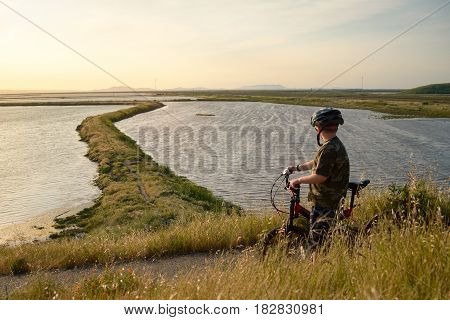 Boy in helmet riding his mountain bike at sunset, enjoying the nature, beautiful trail winding ahead through the bay.