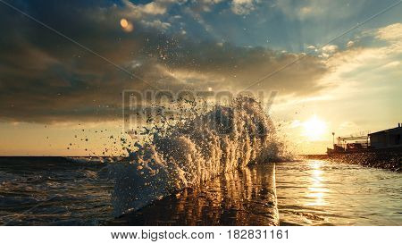 Waves crash into the shore and move along the breakwater against the background of the building and sunset