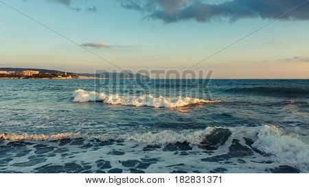 The incoming sea wave against the background of Tolstoy cape coast of Gelendzhik. Seascape on the background of the setting sun. North Caucasus Russia