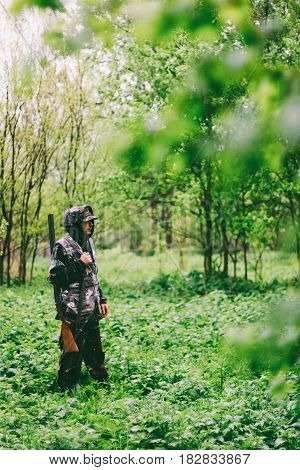 A man hunter wanders with a gun in rainy weather through a spring forest toned photo