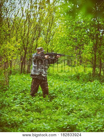 A man hunter take aim for a shot from a carbine hunting in a spring forest in the rain toned photo
