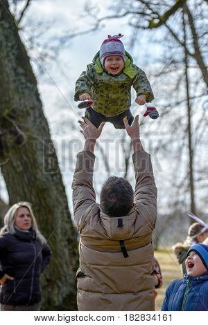 DOLE LATVIA - MARCH 27 2016: Easter holidays. Unknown Man throws children into the air.
