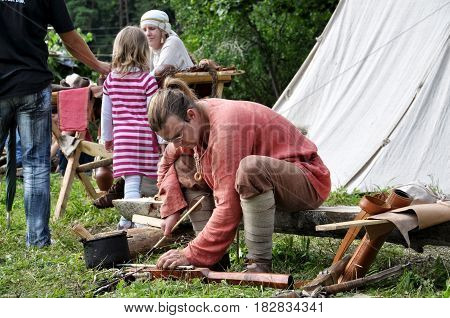 TERVETE LATVIA - AUGUST 13 2011: Historical Zemgalu days. Unknown man in ancient dress sits on a bench and repairing ancient weapons.
