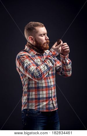 Adult bearded man in checked shirt smoking pipe while looking at camera with one eye