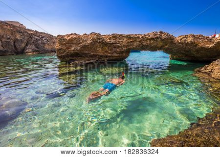 Blue Lagoon Malta - Snorkeling tourist at the caves of the Blue Lagoon on the island of Comino on a bright sunny summer day with blue sky