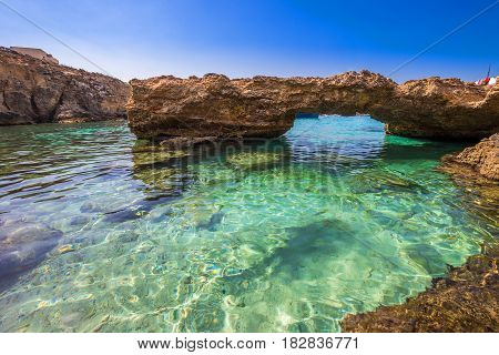 Blue Lagoon Malta - The arch of the Blue Lagoon on the island of Comino on a bright sunny summer day with blue sky