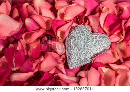 Decorative carved heart at red rose petals background