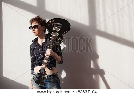 the girl with the short hair with a guitar and glasses