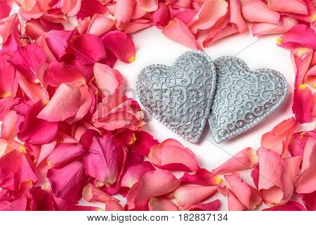 Couple of decorative carved hearts in heart frame shape of red rose petals on white background