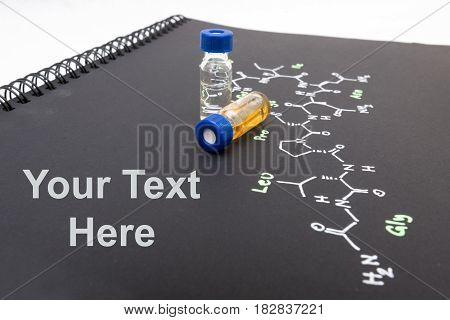 Close-up Blue Cap Sample Vial On Notebook With Chemical Formula Of Oxytocin (love Hormone) With Text