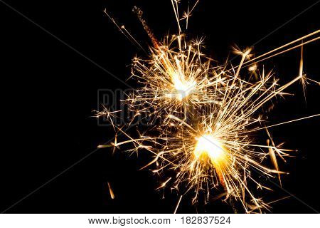 Burning sparkler from both ends at black background isolated