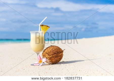 Pina Colada cocktail on the beach with coconut and exotic flower