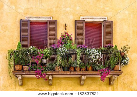 Sunny rustic balcony with flowers in Verona