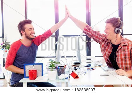 Two young man in office clapping their hands