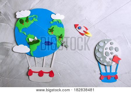 Paper craft earth globe moon flag rocket handmade on gray concrete background. Earth day concept. Horizontal orientation top view.