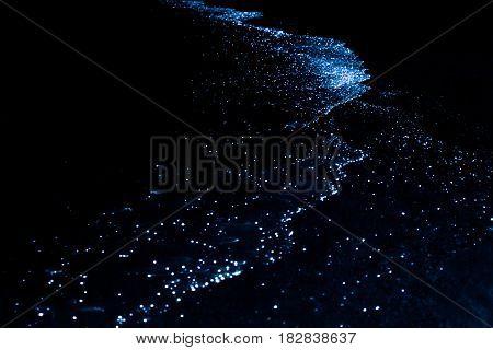 Bio luminescence. Illumination of plankton at Maldives. Many particles at black background.
