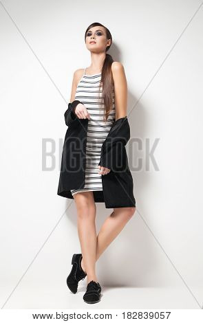 Attractive young woman looking at camera standing in elegant clothes. Vertical studio shot.