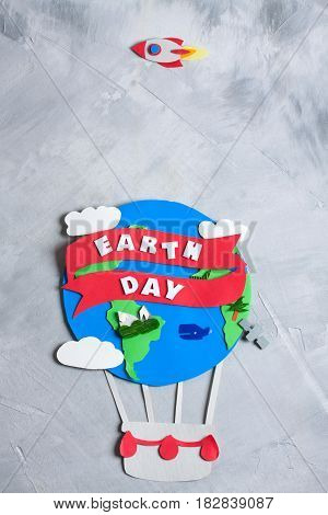 Paper craft earth globe rocket handmade on gray concrete background. Earth day concept lettering text. Vertical orientation top view.