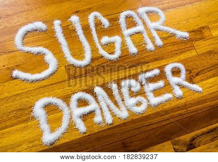Letters with text sugar danger on wooden background