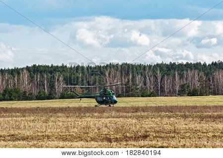 Russia, Tyumen - 15.04.2017: MI-2 helicopter landed on the field near the forest belt