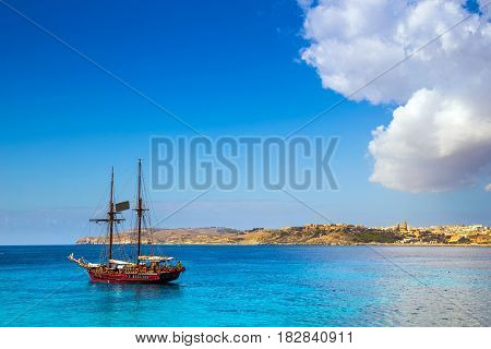 Blue Lagoon Malta - Old sailing boat at the Island of Comino next to the famous Blue Lagoon with the Island of Gozo and town of Mgarr at the background on a sunny summer day