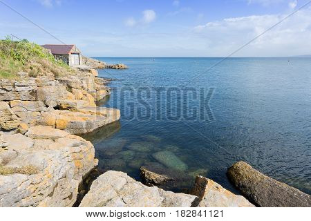 Rocky coastline at Moelfre with old lifeboat station Anglesey North Wales